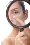 Jonge vrouw die huid met meer magnifier onderzoekt Royalty-vrije Stock Foto's