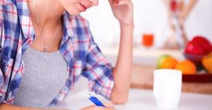 Jonge vrouw die iets in haar notastootkussen schrijven Stock Afbeelding