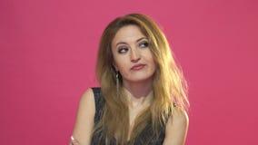 Jonge vrouw die iets kauwen smaakloos op een roze achtergrond stock videobeelden