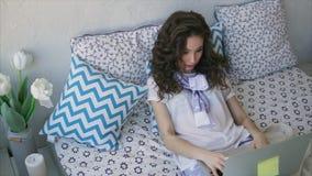 Jonge vrouw die inkomende berichten op laptop post in de slaapkamer doorbladeren stock footage