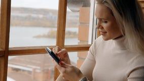 Jonge vrouw die Internet op haar moderne cellulair gebruiken stock video
