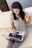 Jonge vrouw die Internet thuis doorbladert Royalty-vrije Stock Afbeeldingen