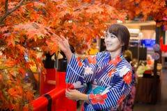 Jonge vrouw die Japanse traditionele kimono in de herfstkleur dragen met rode houten brug royalty-vrije stock foto's