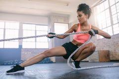 Jonge vrouw die kabel trekken bij gymnastiek Royalty-vrije Stock Afbeelding