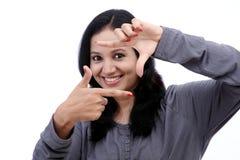 Jonge vrouw die kader met haar handen maken stock afbeelding