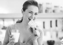 Jonge vrouw die kernachtig brood met melk in keuken eten royalty-vrije stock afbeeldingen
