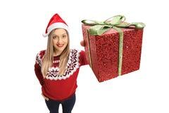 Jonge vrouw die Kerstmis dragen die een heden tonen Stock Foto's