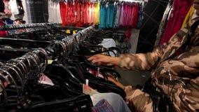Jonge vrouw die kleren in de kledingswinkel kiezen stock video