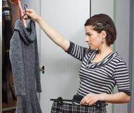 Jonge vrouw die kleren kiest Royalty-vrije Stock Afbeelding