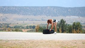 Jonge vrouw die kleren van koffer werpen stock video