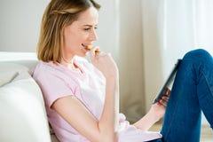 Jonge vrouw die koekje eten en digitale tablet thuis gebruiken royalty-vrije stock afbeelding
