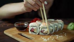 Jonge vrouw die in koffie sushi met eetstokjes eten stock videobeelden