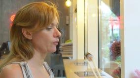 Jonge vrouw die in koffie sushi met eetstokjes eten 4k, close-up stock footage
