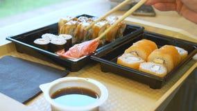 Jonge vrouw die in koffie sushi met eetstokjes eten 4k, close-up stock video