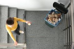 Jonge vrouw die koffiekop in afvalbak binnen werpen, hoogste mening stock afbeelding