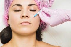 Jonge vrouw die kosmetische injectie in schoonheidskliniek krijgen royalty-vrije stock foto's