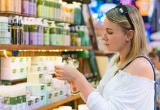 Jonge vrouw die kosmetische room kiezen stock afbeeldingen