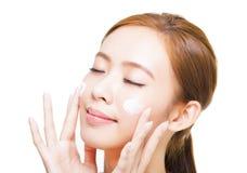 Jonge vrouw die kosmetische room op haar gezicht toepassen Stock Foto's