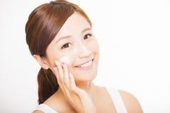 Jonge vrouw die kosmetische room op haar gezicht toepassen Stock Afbeeldingen