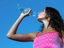 Jonge vrouw die koud water in hete dag drinkt Royalty-vrije Stock Fotografie