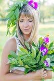 Jonge vrouw die kroon van bloemen en boeket dragen Stock Afbeeldingen