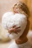 Jonge vrouw die kussen koestert Royalty-vrije Stock Afbeelding