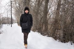 Jonge Vrouw die langs een Sneeuw behandeld Voetpad lopen royalty-vrije stock afbeelding