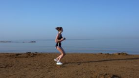 Jonge vrouw die langs een zandig strand bij zonsondergang lopen stock video
