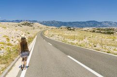Jonge vrouw die langs lege weg lopen Royalty-vrije Stock Afbeeldingen