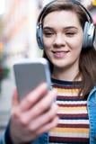 Jonge Vrouw die langs Straat het Stromen Muziek van Mobiele Pho lopen royalty-vrije stock foto