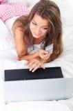 Jonge vrouw die laptop in bed met behulp van Royalty-vrije Stock Afbeeldingen