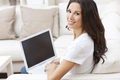 Jonge Vrouw die Laptop Computer thuis op Bank met behulp van stock afbeeldingen
