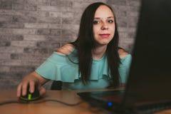 Jonge vrouw die laptop computerzitting voor witte bakstenen muurachtergrond, mensen en technologie, levensstijlen gebruiken royalty-vrije stock afbeeldingen