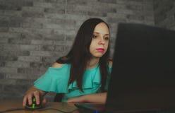 Jonge vrouw die laptop computerzitting voor witte bakstenen muurachtergrond, mensen en technologie, levensstijlen gebruiken stock fotografie