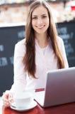 Vrouw die laptop in koffie met behulp van Stock Foto's