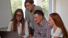 Jonge vrouw die laptop met behulp van, die aan een project met haar klasgenoten werken stock afbeelding