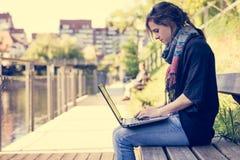 Jonge vrouw die laptop met behulp van bij een riverbank stock afbeeldingen