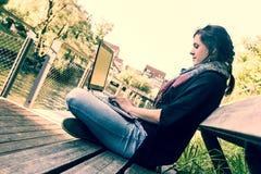 Jonge vrouw die laptop met behulp van bij een riverbank royalty-vrije stock foto
