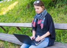 Jonge vrouw die laptop met behulp van bij een riverbank stock fotografie