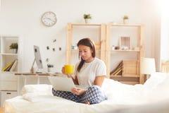 Jonge vrouw die laptop op bed met behulp van stock fotografie