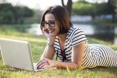 Jonge vrouw die laptop in park met behulp van stock foto
