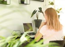 jonge vrouw die laptop thuis met behulp van In ruimtebinnenland met installaties royalty-vrije stock fotografie