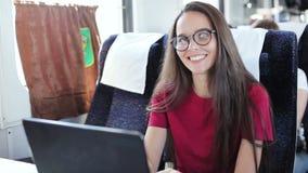 Jonge vrouw die laptop zitting aan de gang gebruiken stock footage