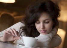 Jonge vrouw die latte van koffie in koffie geniet Stock Afbeeldingen