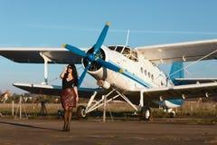 Jonge vrouw die in leerrok dichtbij het vliegtuig in openlucht op de luchthavenbaan lopen stock afbeelding
