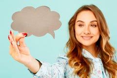 Jonge vrouw die lege gedachte bel over blauwe achtergrond houden royalty-vrije stock fotografie