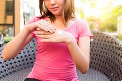 Jonge vrouw die lichaamslotion of room op handen toepassen terwijl het zitten royalty-vrije stock fotografie