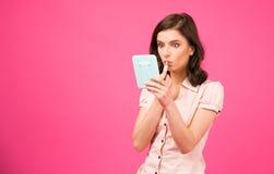 Jonge vrouw die lippenstift op lippen zetten Stock Fotografie