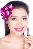 Jonge vrouw die lippenstift op lippen zetten stock afbeelding