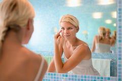 Jonge vrouw die lotion op gezicht thuis toepast stock afbeeldingen